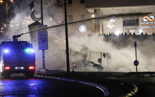 Les forces de sécurité israéliennes aspergent des émeutiers palestiniens avec de l'eau lors de confrontations avec eux dans la ville majoritairement arabe d'Umm al-Fahm, dans le nord d'Israël, le 19 mai 2021. (Crédit : Ahmad GHARABLI / AFP)