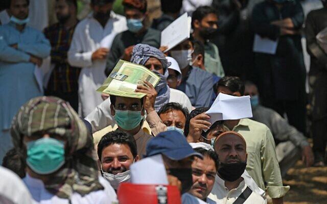 Des ressortissants pakistanais, portant des masques, font la queue pour demander un visa à l'ambassade d'Afghanistan à Islamabad, le 19 mai 2021. L'Afghanistan connaît un afflux improbable de visiteurs en raison de la pandémie de coronavirus. Des milliers de travailleurs pakistanais désespérés transitent par la capitale déchirée par la guerre pour tenter de rejoindre l'Arabie saoudite. (Crédit : Aamir QURESHI / AFP)