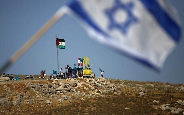 Photo prise le 20 mai 2021, depuis la ville de Metula dans le nord d'Israël, près de la frontière avec le Liban où flotte le drapeau israélien, avec en arrière-plan des gens à la périphérie du village de Kfarkila dans le sud du Liban, brandissant des drapeaux palestiniens, libanais et du Hezbollah, organisation soutenue par l'Iran. (Crédit : Jalaa Marey / AFP)