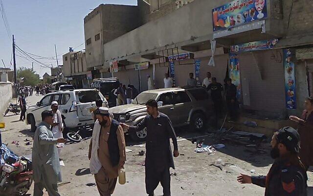 Des responsables de la sécurité et des passants sur les lieux de l'explosion d'une bombe lors d'un rassemblement pro-palestinien, qui a fait six morts et 14 blessés, à Chaman, dans la province pakistanaise du Baloutchistan, près de la frontière afghane, le 21 mai 2021. (Crédit : Asghar ACHAKZAI / AFP)