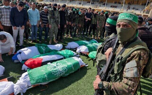 Des Palestiniens prient à côté des corps des membres des brigades Ezzedine Al-Qassam, aile armée du Hamas, morts pendant le bombardement d'un tunnel, lors de leurs funérailles à Khan Younès, dans le sud de la bande de Gaza, le 21 mai 2021. (Crédit :  SAID KHATIB / AFP)