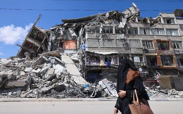 Une Palestinienne passe devant un immeuble détruit dans le quartier commercial d'al-Rimal à Gaza City, suite à une frappe israélienne, après le cessez-le-feu conclu entre Israël et les groupes terroristes palestiniens. (Crédit :Emmanuel Dunand/AFP)