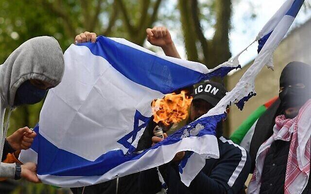 Des activistes propalestiniens et leurs partisans brûlent un drapeau israélien lors d'une manifestation en soutien aux Palestiniens devant l'ambassade d'Israël à Londres, le 22 mai 2021. (Crédit :  JUSTIN TALLIS / AFP)