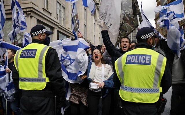 La police maintient un cordon de sécurité alors que des manifestants pro-israéliens se sont rassemblés aux abords de l'ambassade israélienne, dans le centre de Londres, le 23 mai 2021. (Crédit : Tolga Akmen/AFP)