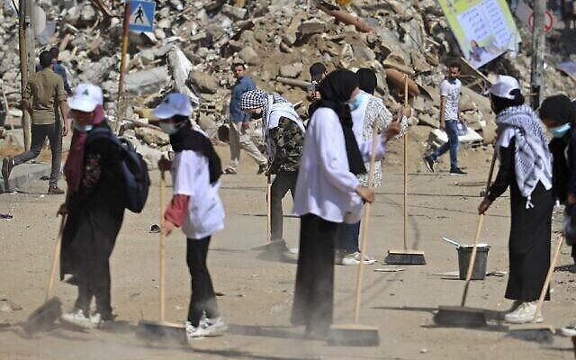 Des volontaires palestiniens balaient la poussière devant un bâtiment détruit lors de la dernière série de combats, dans le quartier Rimal de la ville de Gaza, le 25 mai 2021. (Crédit : MOHAMMED ABED / AFP)