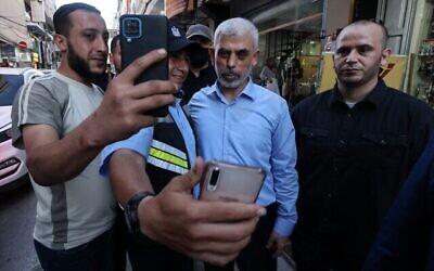 """Yahya Sinwar, chef de l'aile politique du mouvement palestinien Hamas, pose pour un """"selfie"""" avec des partisans alors qu'il visite le quartier d'Al-Rimal dans la ville de Gaza, le 26 mai 2021, pour évaluer les dégâts causés par les récents bombardements des forces israéliennes. (Crédit : MOHAMMED ABED / AFP)"""