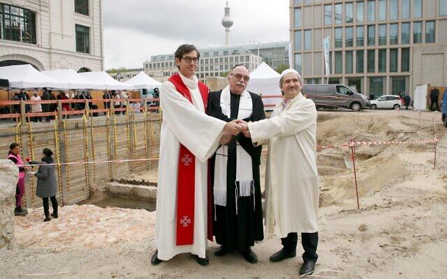 """Le pasteur Gregor Hohberg, le rabbin Andreas Nachama et l'imam Kadir Sanci posent pendant la cérémonie d'inauguration du bâtiment multireligieux """"House Of One"""" le 27 mai 2021. (Crédit : Wolfgang Kumm / dpa / AFP)"""