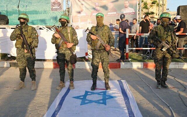 Des membres de l'aile militaire du groupe terroriste du Hamas piétinent un drapeau israélien à Khan Yunis, dans le sud de la bande de Gaza, le 27 mai 2021, alors que le Hamas revendique la victoire après un conflit de 11 jours avec Israël. (Crédit : SAID KHATIB / AFP)
