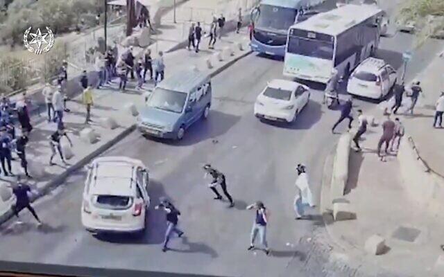 Des émeutiers arabes jettent des pierres sur un véhicule, dans la Vieille Ville de Jérusalem, le 10 mai 2021. (Crédit :  capture d'écran Twitter)