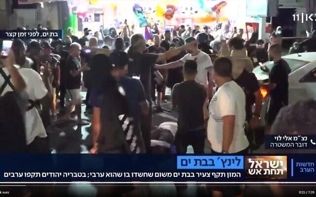 Un homme présumablement arabe lynché par la foule à Bat Yam, en direct à la télévision, le 21 mai 2021. (Capture d'écran Kan)