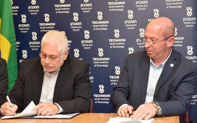 De gauche à droite, le président du Technion, le professeur Uri Sivan, signe l'accord de collaboration avec l'hôpital Israelita Albert Einstein de Sao Paulo, au Brésil, et le professeur Alon Wolf, responsable du développement des ressources, le 6 mai 2021. (Crédit : Sharon Tzur, bureau du porte-parole du Technion)