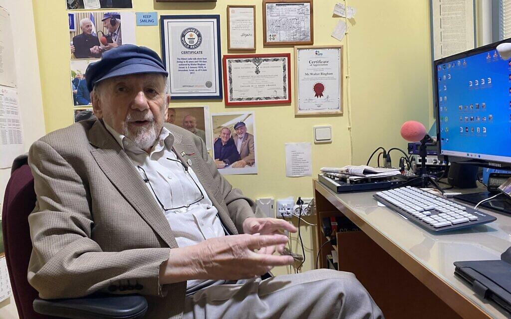 Le journaliste de radio Walter Bingham assis à son bureau de Jérusalem, de multiples souvenirs accrochés au mur, notamment un télégramme concernant une récompense donnée par le roi britannique George VI. (Sam Sokol/ JTA)