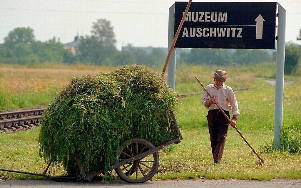 """Un jardinier travaille à côté des voies ferrées qui mènent à Auschwitz. Image tirée du documentaire de 1998 """"Le dernier jour"""". (Autorisation)"""