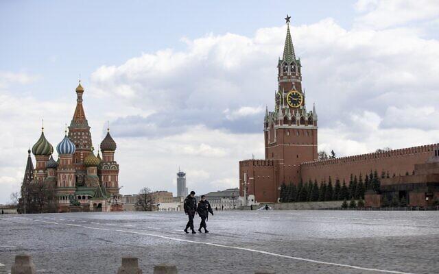 Deux officiers de police patrouillent sur une Place Rouge presque vide, avec la cathédrale Saint-Basile, au centre, et la tour Spasskaya à Moscou, en Russie, le 20 avril 2020. (Crédit : AP Photo/Alexander Zemlianichenko)