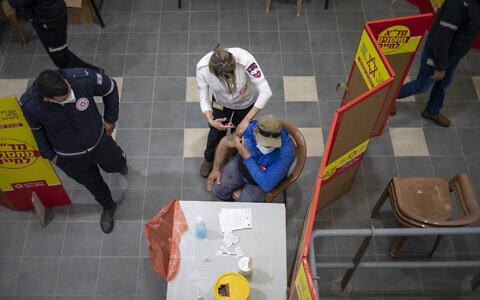 Un ouvrier palestinien qui travaille en Israël reçoit sa première dose du vaccin Moderna COVID-19 dans un centre de vaccination contre le coronavirus installé au poste de contrôle de Gilboa, entre Israël et la ville de Jénine en Cisjordanie, le 8 mars 2021. (AP Photo/Ariel Schalit)