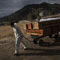 Un employé des pompes funèbres tire des cercueils vides qui transportaient des corps qui ont été incinérés au cimetière La Recoleta  à Santiago, au Chili, dans le cadre de la pandémie de coronavirus, le 21 avril 2021. (Crédit : AP Photo/Esteban Felix)