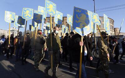 Des manifestants brandissent les emblèmes de la 14e division de grenadiers Waffen de la SS à Kiev, en Ukraine, le 28 avril 2021. (AP Photo/Efrem Lukatsky)