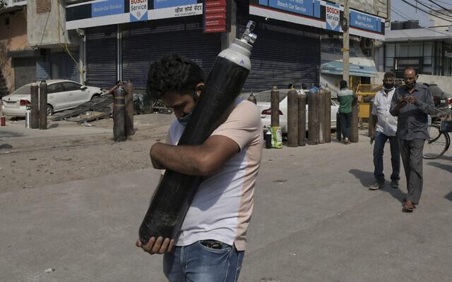 Un homme marche en portant une bonbonne d'oxygène remplie pendant que les membres de la famille des patients du COVID-19 font la queue pour remplir leur bouteille d'oxygène dans le quartier de Mayapuri à New Delhi, en Inde, le 3 mai 2021. (Crédiy : Ishant Chauhan/AP)