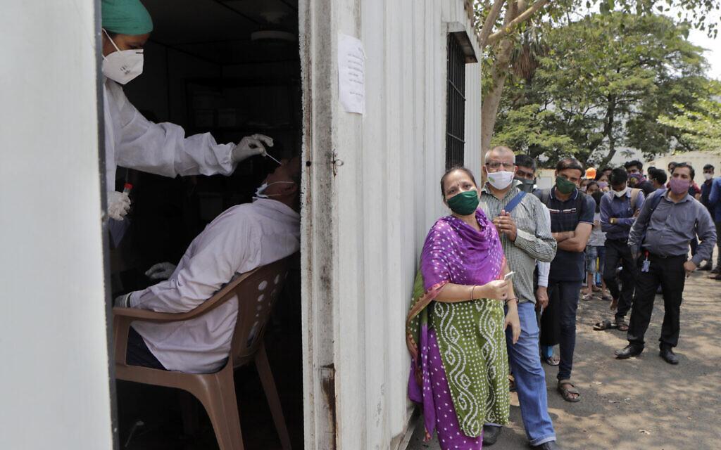 Un employé prélève un échantillon nasal pour un test à la COVID-19 dans un hôpital de campagne de Mumbai, en Inde, le 6 mai 2021. (Crédit : AP Photo/Rajanish kakade)