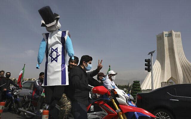 Un manifestant en moto tient une effigie représentant Israël et les États-Unis lors d'un rassemblement annuel de la Journée al-Quds à Téhéran, en Iran, le 7 mai 2021. (Crédit :  AP Photo/Vahid Salemi)