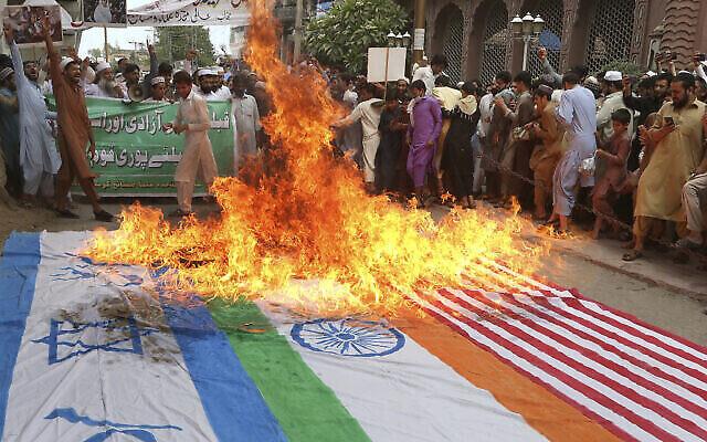 Des manifestants scandent des slogans après avoir brûlé des représentations des drapeaux américain, indien et israélien pendant la journée annuelle al-Quds à Peshawar, au Pakistan, le 7 mai 2021. (Crédit : AP Photo/Muhammad Sajjad)