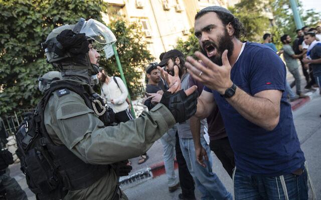 La police anti-émeute israélienne fait face à un homme juif alors que des affrontements ont éclaté entre Arabes, policiers et Juifs, dans la ville mixte de Lod, dans le centre d'Israël, mercredi 12 mai 2021. (Crédit : AP Photo/Heidi Levine)