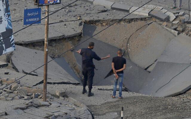 Des personnes se tiennent dans une rue détruite par une frappe aérienne israélienne dans la ville de Gaza en réponse à un tir de roquette, le 13 mai 2021 (Crédit : AP Photo/Hatem Moussa).