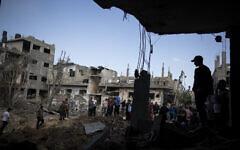 Des Palestiniens inspectent des maisons détruites par les frappes israéliennes nocturnes dans le nord de la bande de Gaza en représailles aux tirs de roquettes sur Israël, le 14 mai 2021. (Crédit : AP Photo/Khalil Hamra)