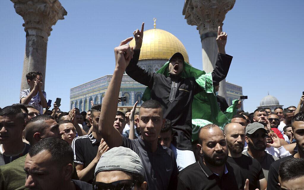 Un fidèle musulman arbore un drapeau du Hamas lors d'une manifestation contre Israël après les prières du vendredi, près du Dôme du Rocher, mosquée dans l'enceinte de la mosquée Al-Aqsa sur le mont du Temple dans la Vieille Ville de Jérusalem, le vendredi 14 mai 2021. (AP Photo / Mahmoud Illean)