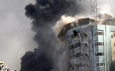 La tour hébergeant les bureaux de l'Associated Press et d'autres médias à Gaza s'effondre après une frappe israélienne, le 15 mai 2021. (Crédit :AP/Hatem Moussa)