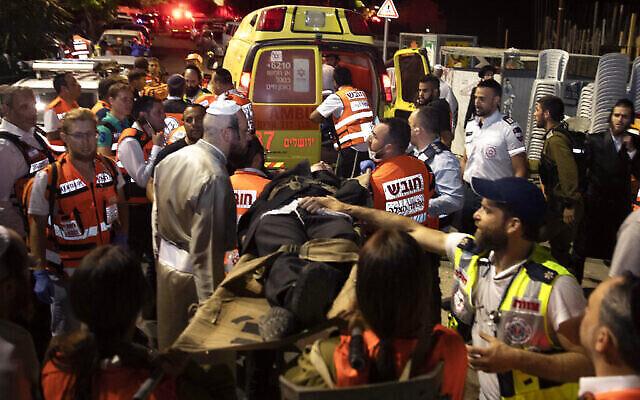 Des médecins israéliens transportent des hommes ultra-orthodoxes blessés, devant une synagogue de Givat Zeev, près de Jérusalem, le dimanche 16 mai 2021 ; plus de 150 personnes ont été blessées dans l'effondrement fatal d'un gradin dans une synagogue inachevée de Cisjordanie. (Photo AP / Sebastian Scheiner)