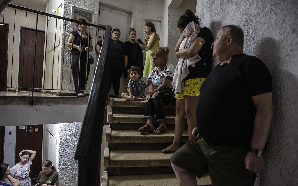 Des Israéliens se réfugient dans la cage d'escalier de leur immeuble alors qu'une sirène retentit pour avertir de l'arrivée de roquettes tirées depuis la bande de Gaza, à Ashdod, le 19 mai 2021. (Crédit : AP Photo/Heidi Levine)