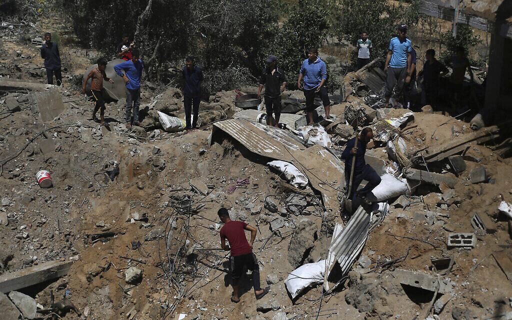 Des Palestiniens inspectent les dégâts d'une maison détruite par une frappe aérienne israélienne dans la ville de Khan Younis, dans le sud de la bande de Gaza, mercredi 19 mai 2021. (Crédit : AP Photo/Yousef Masoud)
