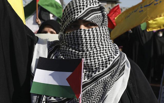 Photo d'illustration : Une femme, le visage couvert comme le sont les militants palestiniens et libanais, tient un drapeau propalestinien lors d'un rassemblement à Téhéran, le 19 mai 2021. (Crédit : AP Photo/Vahid Salemi)