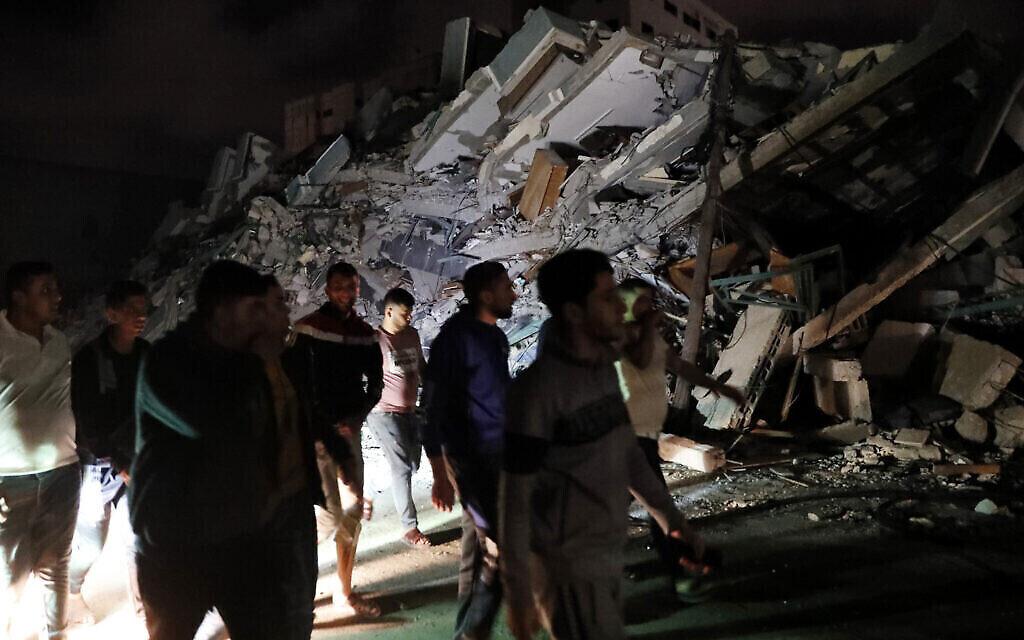 Des Palestiniens célèbrent l'accord de cessez-le-feu entre Israël et le Hamas en passant devant les décombres d'un bâtiment détruit dans la ville de Gaza, le 21 mai 2021. (Crédit : AP Photo/Adel Hana)