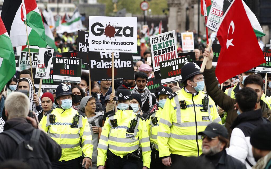 Des manifestants brandissent des pancartes et des banderoles lors d'un rassemblement pro-palestiniens à Londres, samedi 22 mai 2021. (Crédit : AP Photo/Alastair Grant)