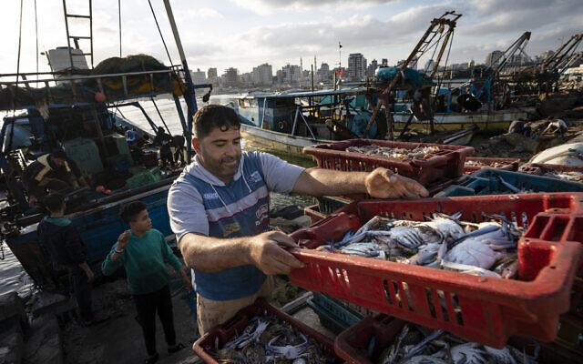 Des pêcheurs chargent une charrette tirée par des chevaux avant de livrer leur butin au marché, après qu'un nombre limité de bateaux a été autorisé à retourner en mer suite à un cessez-le-feu conclu après une guerre de 11 jours entre le Hamas et Israël, dans la ville de Gaza, le 23 mai 2021. (Crédit : AP Photo/John Minchillo)