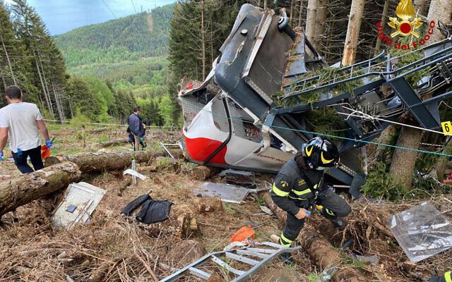 Des sauveteurs travaillent près de l'épave d'un téléphérique qui s'est effondré près du sommet de la ligne Stresa-Mottarone dans la région du Piémont, dans le nord de l'Italie, le 23 mai 2022. (Crédit : sapeurs-pompiers italiens via AP)