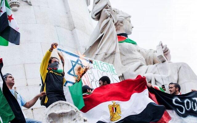 Illustration : un manifestant pro-palestinien brandit un drapeau israélien en feu lors d'une manifestation sur la place de la République à Paris, en France, le 26 juillet 2014. (Crédit : AP Photo/Benjamin Girette)
