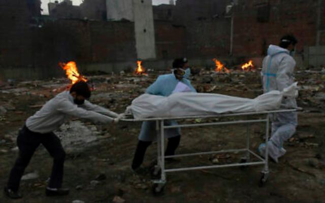 Le corps d'une victime du COVID-19 est emmené pour être incinéré dans un terrain qui a été converti en crématorium à New Delhi, en Inde, le 6 mai 2021 (Crédit : AP Photo / Ishant Chauhan)
