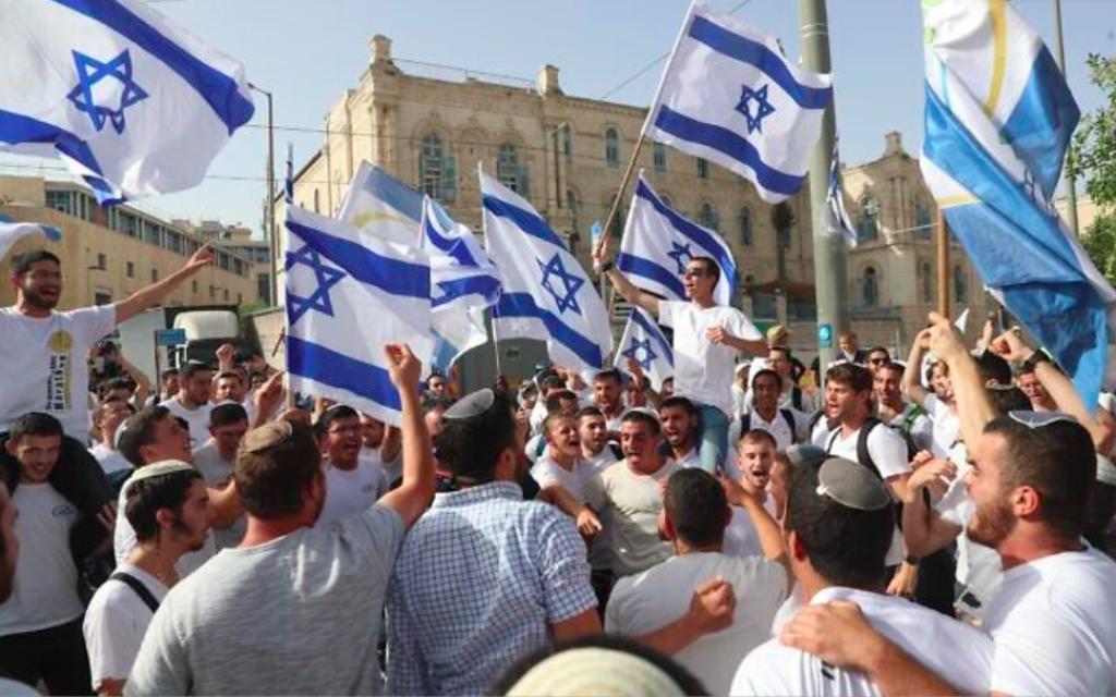 Des Israéliens agitent des drapeaux lors d'une marche à l'occasion de Yom Yeroushalayim, à Jérusalem, le 10 mai 2021 (Crédit : AP Photo / Ariel Schalit)