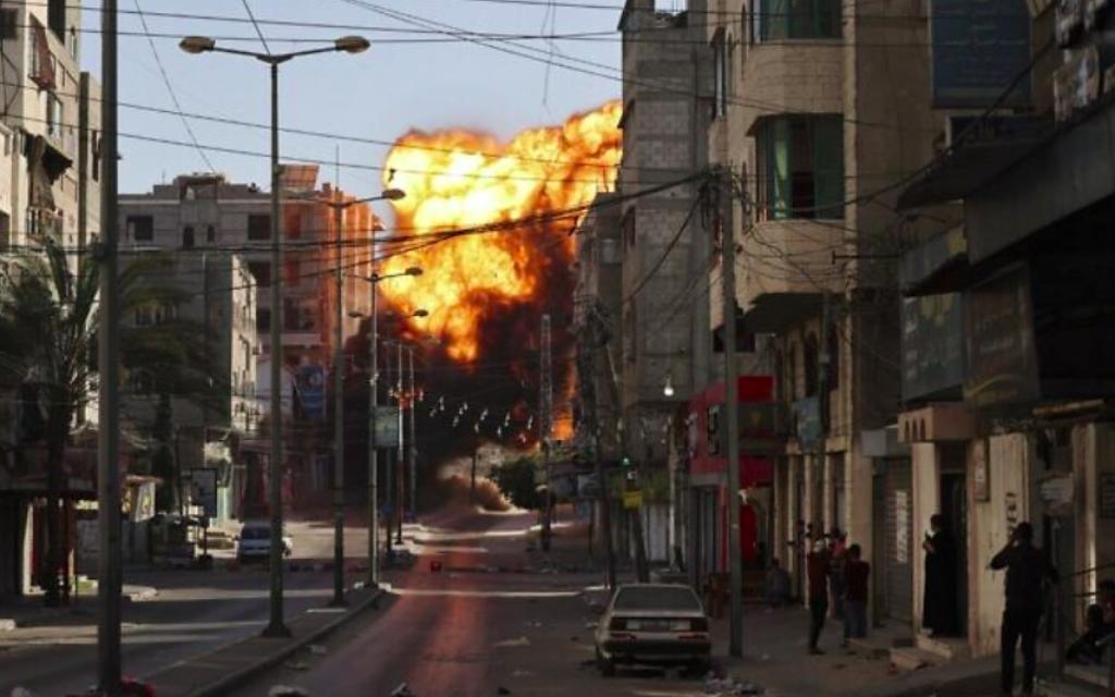 De la fumée noire s'échappe après une frappe aérienne israélienne sur Gaza City visant la banque Intaj liée au Hamas le 14 mai 2021 (Crédit : MOHAMMED ABED / AFP)