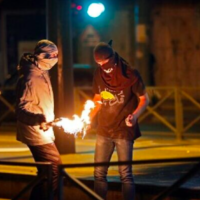 Photo d'illustration : Des émeutiers palestiniens allument un cocktail Molotov lors d'affrontements avec les forces israéliennes dans le quartier de Shuafat à Jérusalem-Est le 14 mai 2021 (Ahmad GHARABLI / AFP)