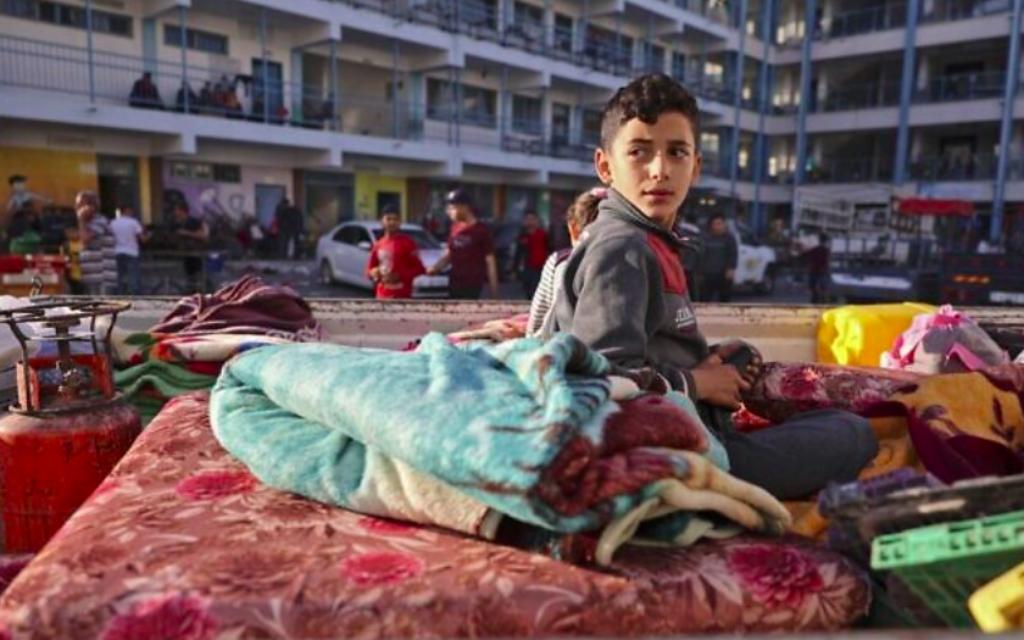 Un garçon palestinien qui a fui son domicile en raison des frappes aériennes israéliennes, menées en guise de représailles aux pluies de roquettes des groupes terroristes palestinien de Gaza visant Israël, est assis sur un matelas devant une école accueillant des réfugiés dans la ville de Gaza, le 14 mai 2021 (Crédit : MOHAMMED ABED / AFP)