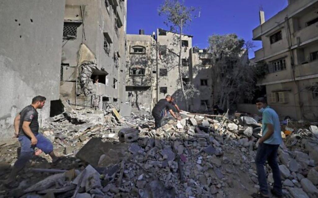Des Palestiniens recherchent des biens à récupérer parmi les décombres d'un immeuble suite aux frappes aériennes israéliennes menées dans Gaza city après des pluies de roquettes du groupe terroriste palestinien du Hamas, à la tête de l'enclave, le 15 mai 2021 (Crédit : MAHMUD HAMS / AFP)