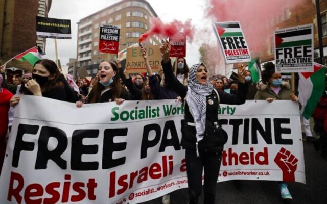 Des militants et partisans pro-palestiniens à Londres lancent des torches de fumée, agitent des drapeaux et brandissent des pancartes lors d'une manifestation contre Israël au milieu des combats entre l'État juif et les terroristes palestiniens à Gaza, le 15 mai 2021 (Crédit : Tolga Akmen / AFP)