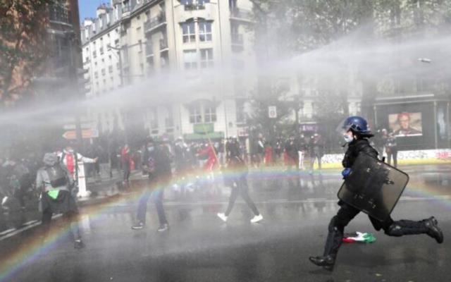 Un policier français court vers des manifestants pro-palestiniens qui manifestent à Paris malgré une interdiction des autorités françaises, le 15 mai 2021 (Geoffroy Van Der Hasselt / AFP)