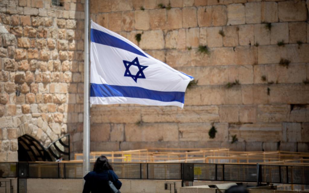 Les gens marchent à côté d'un drapeau israélien en l'honneur des victimes du mont Meron, victimes de la catastrophe, au mur Occidental dans la Vieille Ville de Jérusalem, le 2 mai 2021 (Crédit : Yonatan Sindel / Flash90)