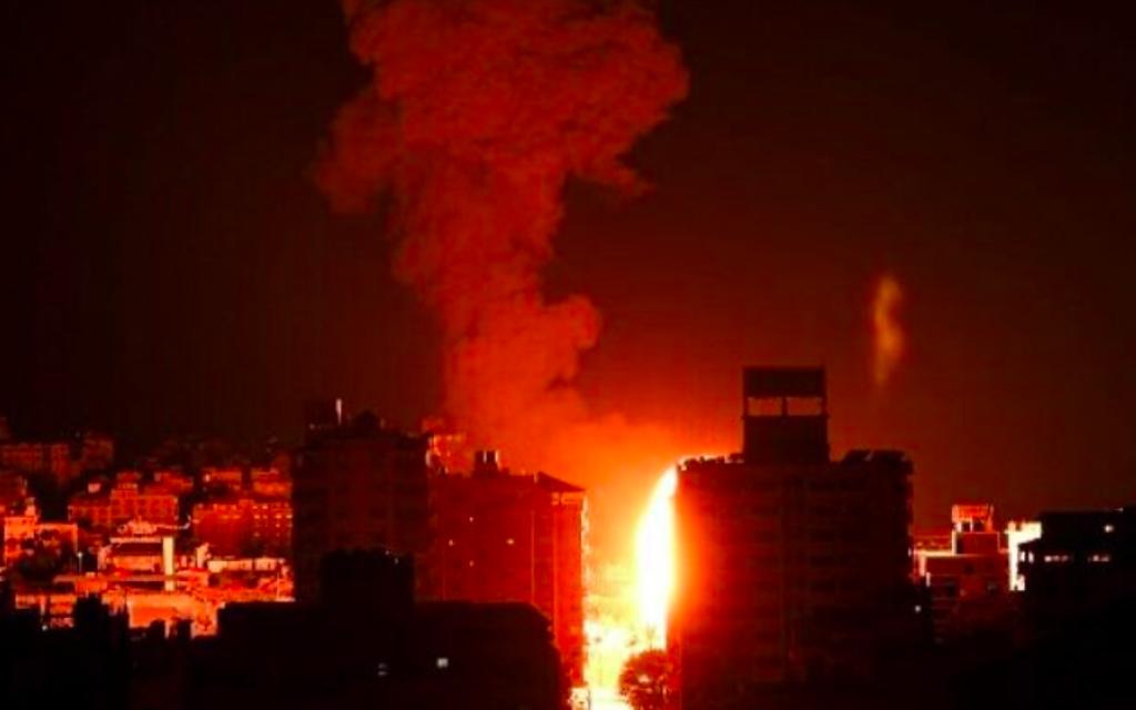 Le feu et la fumée s'élèvent au-dessus des bâtiments de la ville de Gaza alors que les avions de combat israéliens effectuent des frappes en représailles aux roquettes tirées par le Hamas, tôt le 17 mai 2021 (Crédit : MAHMUD HAMS / AFP)
