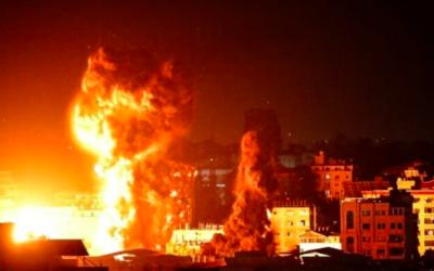 Le feu et la fumée s'élèvent au-dessus des bâtiments de la ville de Gaza alors que les avions de combat israéliens effectuent des frappes en représailles aux roquettes tirées par le Hamas, tôt le 17 mai 2021. (Crédit : Anas Baba/AFP)